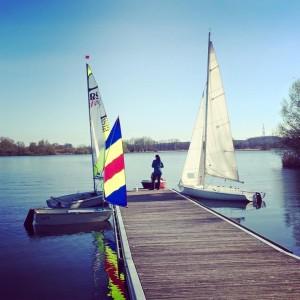 Vier Boote liegen am Steg, zwei große Segelboote, ein kleines Segelboot und ein kleines Motorboot.
