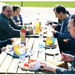 Vereinsmitglieder sitzen draußen am Gedeckten Tisch und essen.